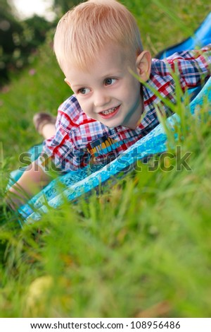 Happy cheerful child lying is among the green grass in a meadow - stock photo