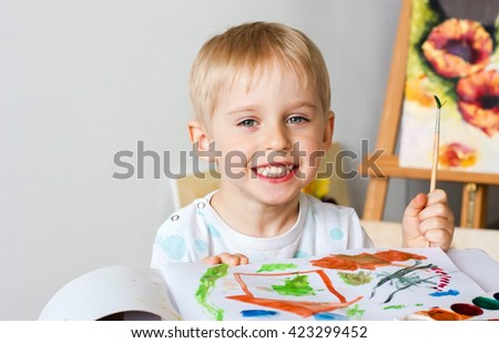 Happy cheerful child paint with brush in album using a lot of tools for drawing. Creativity concept boy draws paints and holds a brush, a happy childhood, soft focus - stock photo