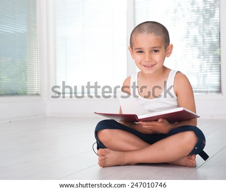 Happy cheerful child with book - stock photo