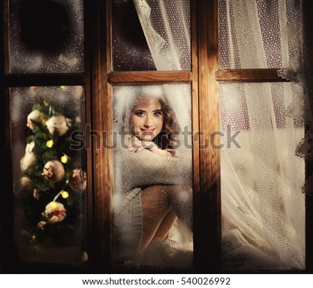 happy cheerful girl  looking through the frozen window, view from outside