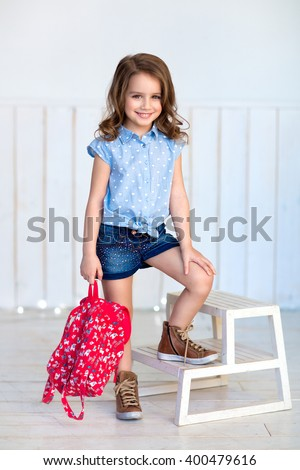 Happy cheerful little girl with curly brown hair in denim shorts and a blue shirt and sneakers standing on a wooden staircase with a pink backpack in hand - stock photo
