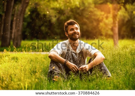 Happy cheerful man sitting on a grass at the park, smiling and lost in thoughts - stock photo