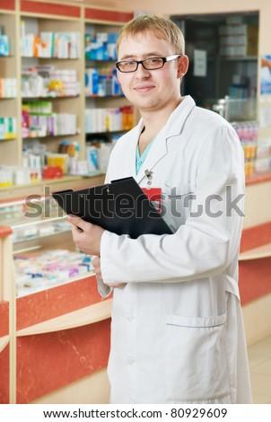 Happy cheerful pharmacist chemist man standing in pharmacy drugstore - stock photo
