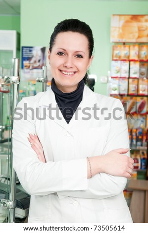Happy cheerful pharmacist chemist woman standing in pharmacy drugstore