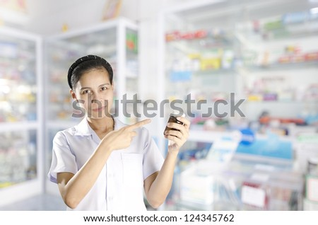 Happy cheerful pharmacist chemist woman standing in pharmacy drugstore with pill bottle - stock photo