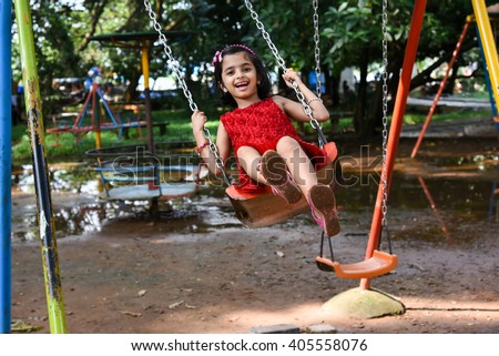Happy cheerful smiling cute little girl/ child/ kid swinging in park, Kerala, India. Naughty playful young Indian daughter enjoying evening day out, on rainy day on vacation. Playing school play area - stock photo