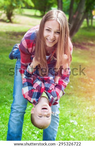 Happy Cheerful Smiling Mother with Boy playing on Summer Meadow.  Lifestyle concept. Both in identical shirts and jeans - stock photo