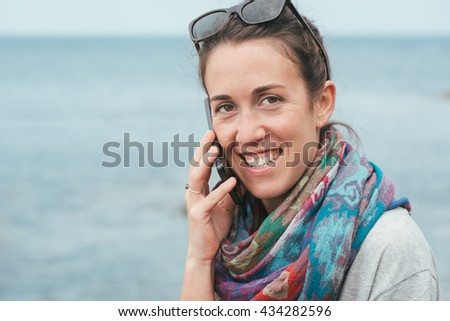 happy cheerful woman by the sea talking on phone with sunglasses on sunny day - stock photo