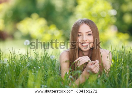 happy cheerful woman laying in green grass