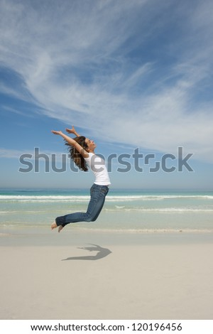 Happy cheerful young attractive woman jumping full of excitement at beach with arms up, isolated with ocean and blue sky as background and copy space. - stock photo