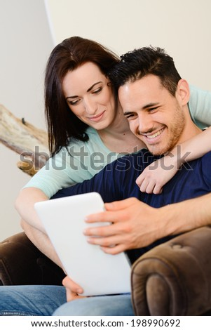 happy cheerful young couple at home playing with digital tablet together - stock photo