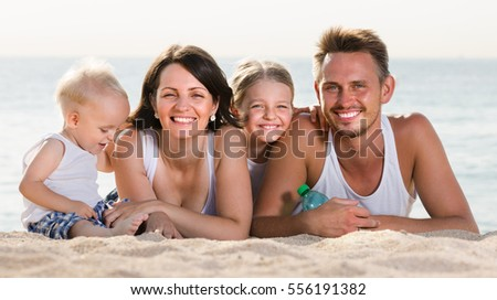 happy cheerful young couple with two children relaxing on beach in sunlight