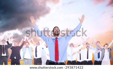 Happy cheering businessman raising his arms against orange and blue sky with clouds - stock photo