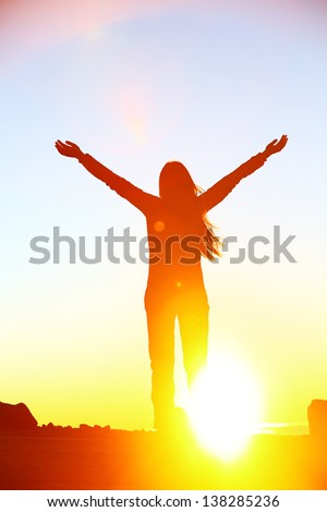 Happy cheering celebrating success woman at beautiful sunset above the clouds. Girl enjoying view of colorful sunset with arms raised up towards the sky. Happy free freedom concept image outdoors. - stock photo