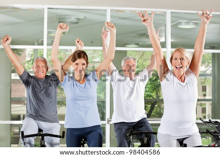 Happy cheering senior group in fitness center on bikes - stock photo