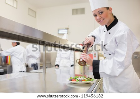 Happy chef cooking a salad with pepper in the kitchen - stock photo