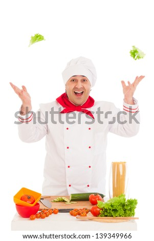 happy chef holding leaf of salad and cooking with fresh vegetables  wearing red and white uniform over white background