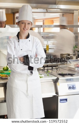 Happy chef leaning against stove in kitchen
