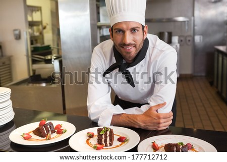 Happy chef looking at camera behind counter of desserts in a commercial kitchen - stock photo
