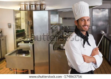 Happy chef looking at camera with arms crossed holding ladle in a commercial kitchen - stock photo