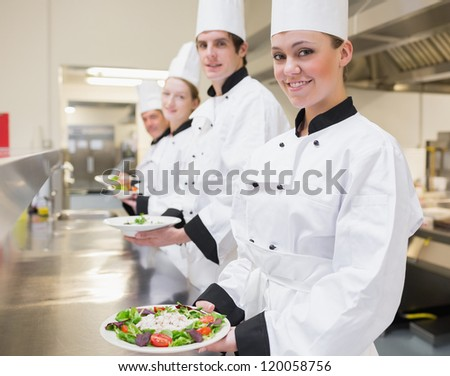 Happy Chef's showing their salads in the kitchen - stock photo