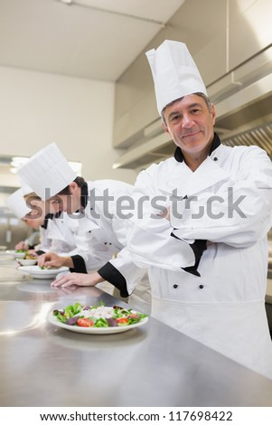Happy chef with others preparing salads in the kitchen - stock photo