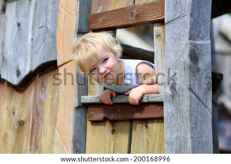 Happy child, adorable blonde toddler girl, having fun outdoors at the park hiding in wooden playhouse in playground on a sunny summer day - stock photo