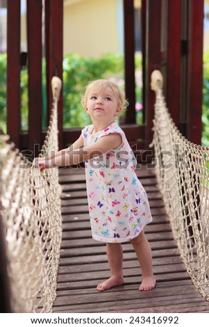 Happy child, adorable blonde toddler girl, having fun outdoors climbing in playground on a sunny summer day - stock photo