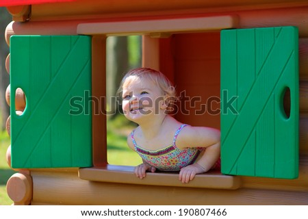 Happy child, adorable blonde toddler girl, having fun outdoors hiding in plastic playhouse in playground on a sunny summer day - stock photo