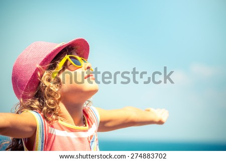 Happy child against blue sky background. Summer vacation concept - stock photo