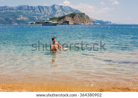 Happy child and father playing in sea - stock photo