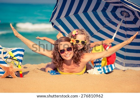 Happy child and mother lying on the beach. Summer vacation concept - stock photo