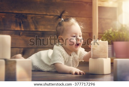 happy child  baby girl playing with blocks and having fun. - stock photo