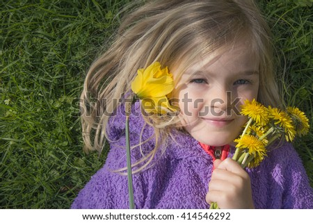 Happy child blond girl lying on grass. Funny kid playing in park. Beautiful spring flowers. Top view portrait. - stock photo