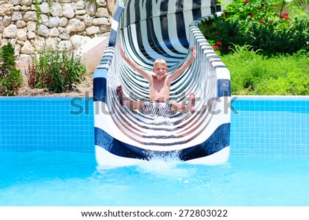 Happy child, blonde teenage boy having fun on water slide in a outdoors swimming pool on sunny day during summer vacation in a beautiful tropical resort