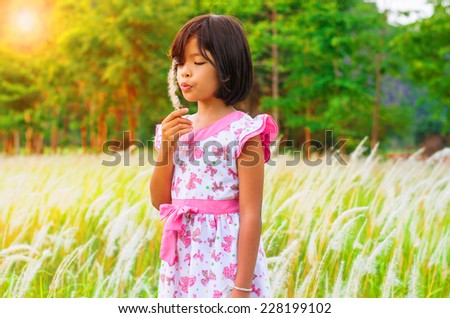 Happy child blowing white flower  outdoors in spring park  - stock photo