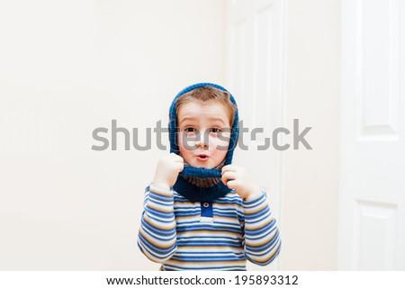 Happy child boy wearing winter hat indoors - stock photo