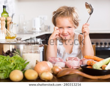 Happy child cooking soup at home kitchen - stock photo