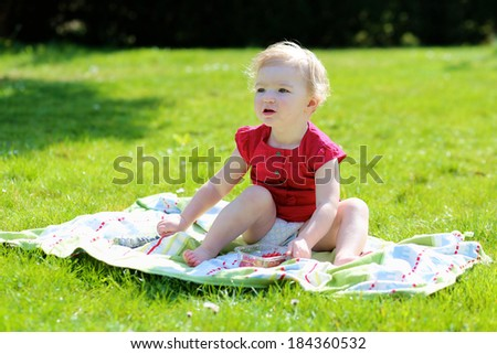 Happy child, cute blonde toddler girl, enjoying healthy snack outdoors eating tasty sweet blueberries and redcurrants sitting on the blanket in the garden on a sunny summer day - stock photo