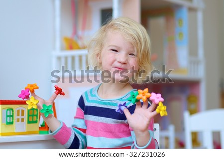 Happy child, cute blonde toddler girl having fun playing with colorful plastic blocks building house indoors at home, school or kindergarten