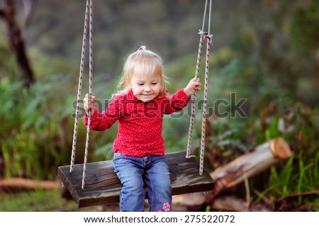 Happy child, cute little baby or toddler girl with blonde curly hair swinging on a wooden swing outdoors in a garden  - stock photo