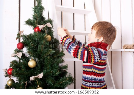 Happy child decorating the Christmas tree with balls. Christmas Eve concept. - stock photo