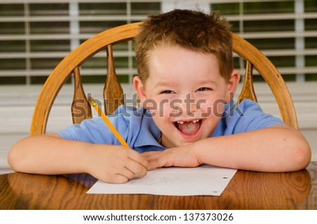 Happy child doing his homework at kitchen table at home - stock photo