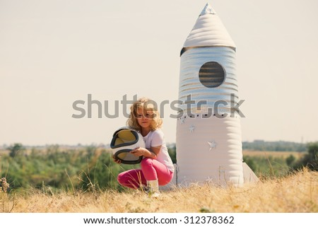 Happy child dressed in an astronaut costume playing with hand made rocket. Summer outdoor. Retro tinted - stock photo