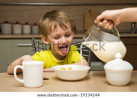Happy child eating breakfast - stock photo