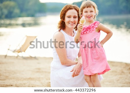 Happy child eating ice cream cone on beach in summer