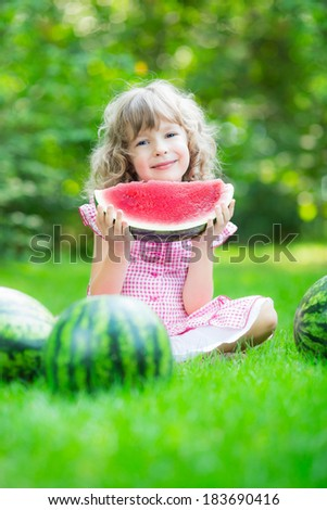 Happy child eating watermelon outdoors in summer park - stock photo
