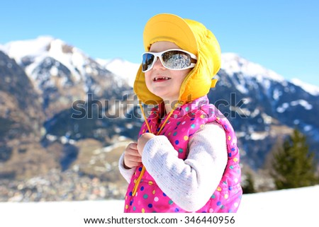 Happy child enjoying winter holidays in Alpine resort in Austria. Little girl playing in the snow. Active toddler learning to ski. Kids having fun outdoors. Beautiful Alps mountains in the background. - stock photo