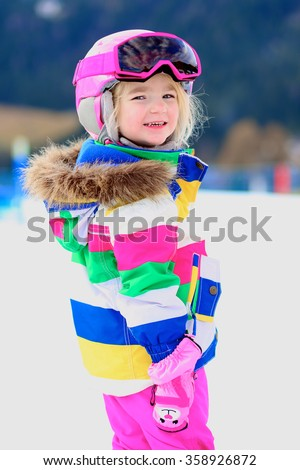 Happy child enjoying winter vacation in Alpine resort in Austria. Little girl playing in the snow. Active sportive toddler learning to ski. - stock photo