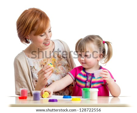 Happy child girl and mother playing with colorful clay toy